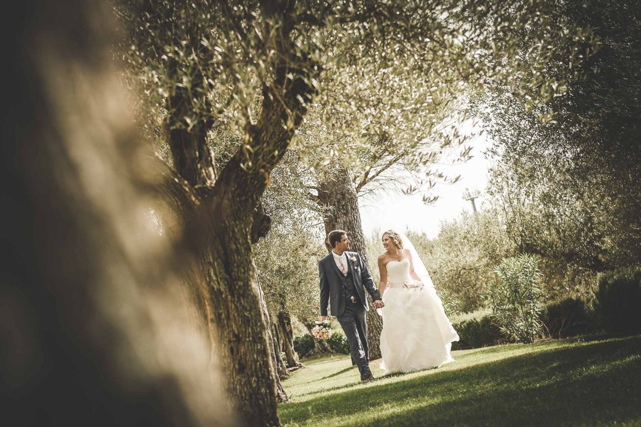 Garden villa wedding Italy. Romantic walk for bride and groom on the grass among the olive trees of the villa.