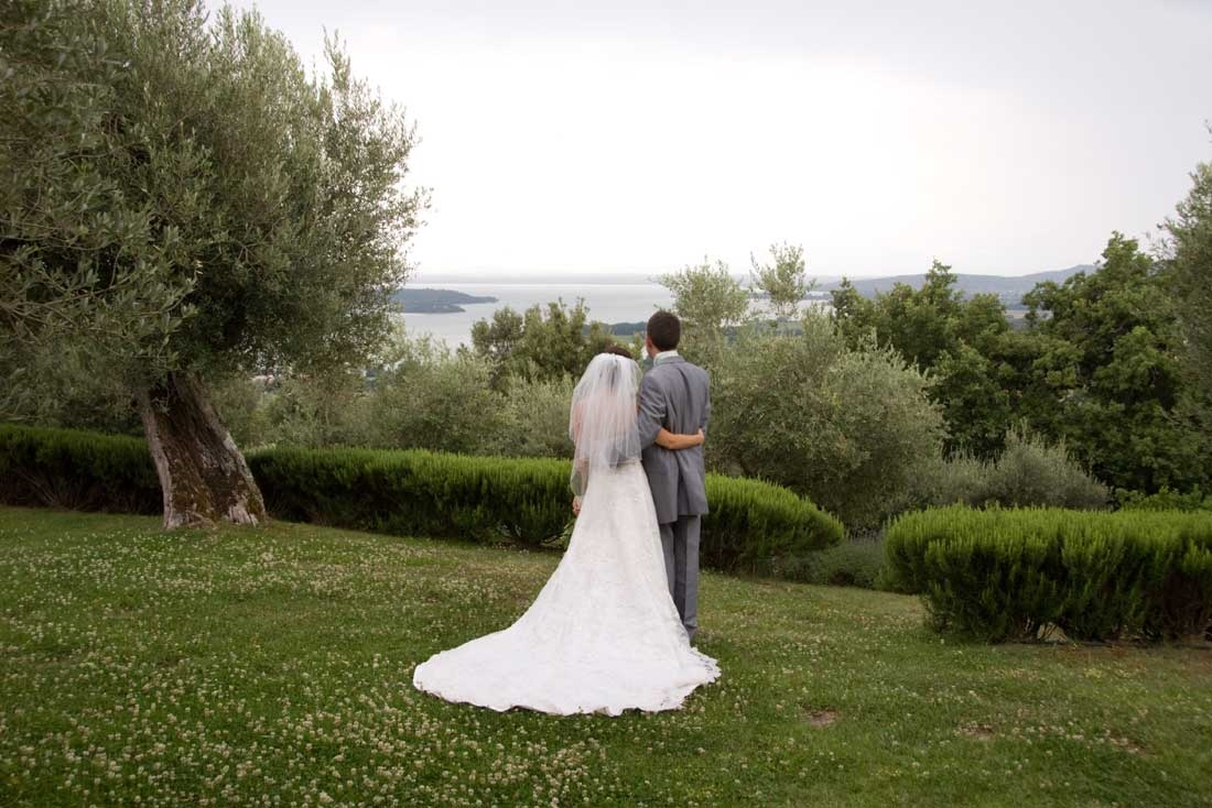 Garden villa wedding Italy. Wedding couple admiring the view over Lake Trasimeno