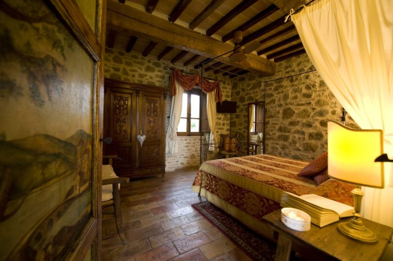 Painted door viewing the bedroom with antique bed and wooden wardrobe and window. wedding tuscany villa