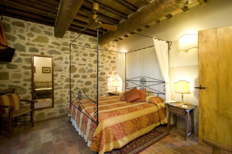 View of one of the bedrooms with iron bed structure, wooden mirror and elegant smooth lighting. wedding tuscany villa