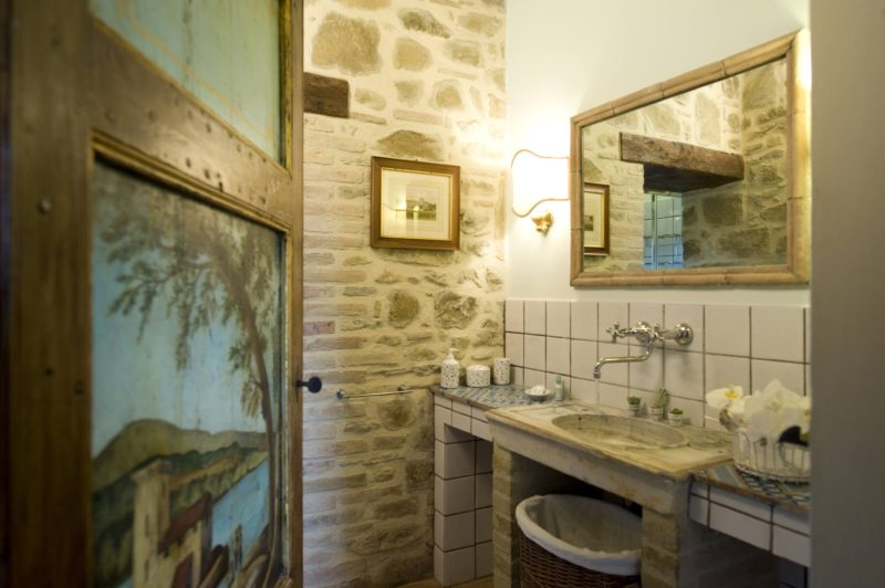 Original painting door with a view to the bathroom, marble sink and mirror. wedding tuscany villa