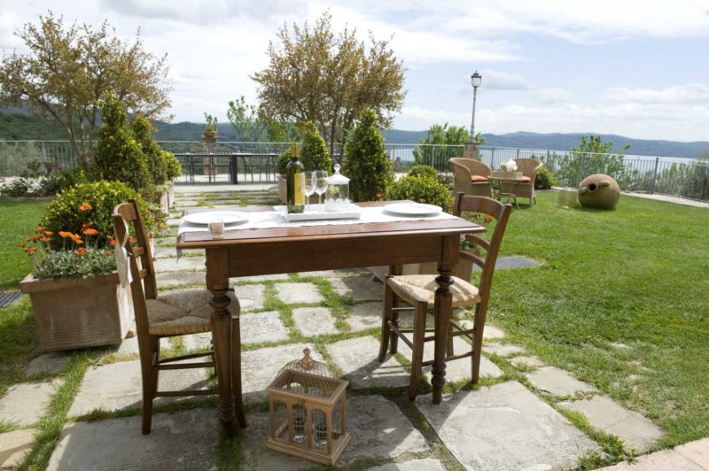 Wooden table and chairs for an intimate lunch overlooking Lake Trasimeno. wedding villa tuscany