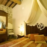 One of the 4 bedrooms, each room has antique terracotta floors and original wooden beams.villa wedding Italy