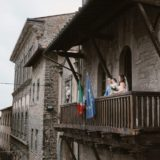 Bridal couple and their daughter on the balcony in Cortona town hall