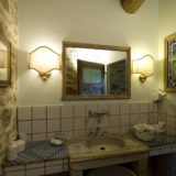 View of the bathroom with the marble sink, mirror, hairdryer and welcome set of soap and shampoo. wedding tuscany villa