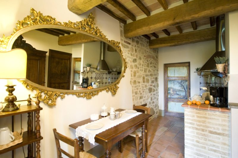 Oval antique mirror amd view of the kitchen area with table and chairs. wedding tuscany villa