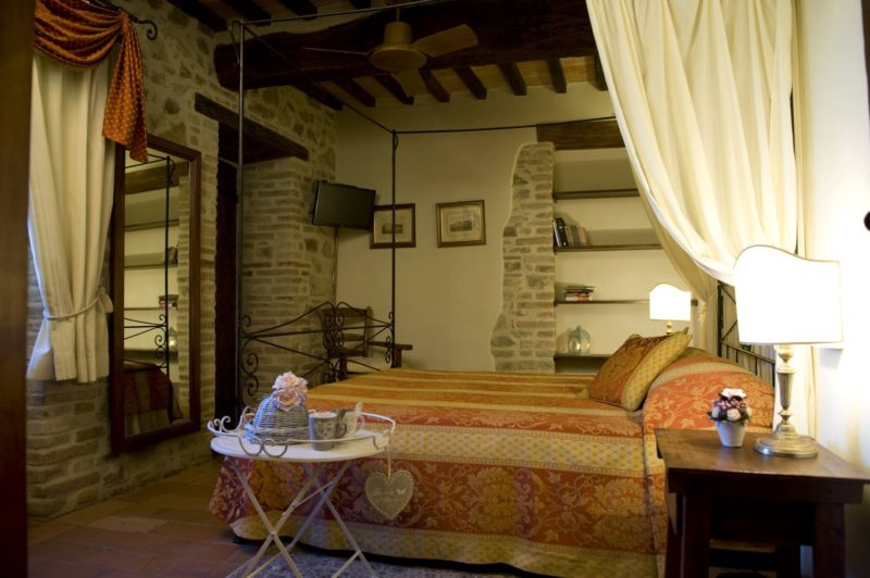 View of one of the bedrooms, flat screen TV, antique bed and wooden furniture. wedding villa tuscany