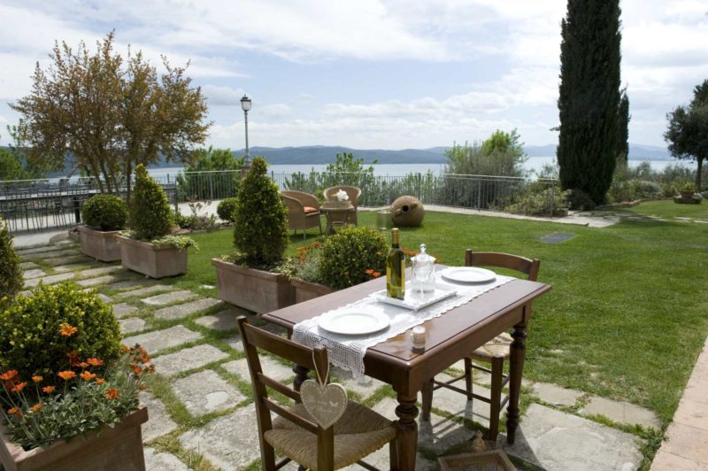 Lovely outdoor furniture enjoying the villa's exclusive garden and amazing view over Lake Trasimeno.villa wedding Italy