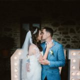 Romantic moment for bride and groom with Love Letters decorations as a background